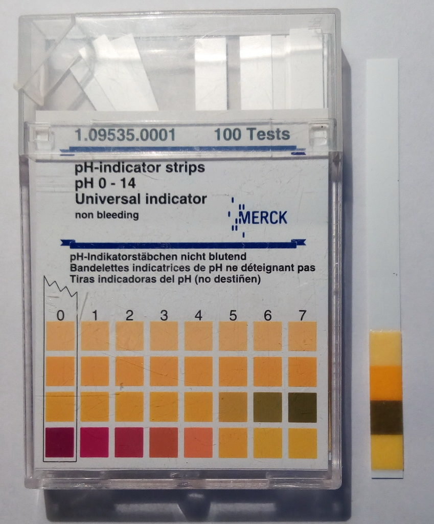 Muestra de saliva comparada con escala indicador de pH. Saliva sample compared with pH indicator scale.